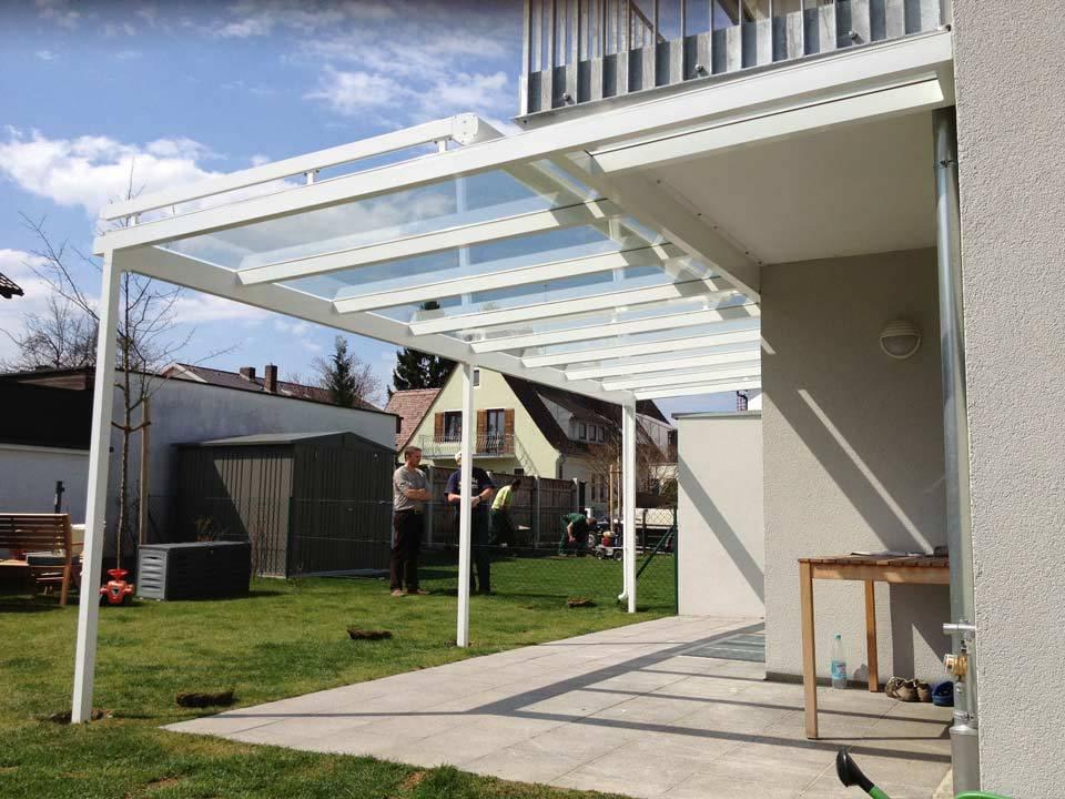 Fertigstellung einer Terrassenüberdachung aus weißem Metall und Glas