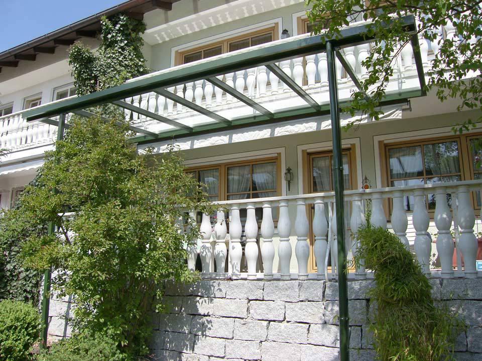 errasse umrahmt von Pflanzen, mit Glasüberdachung aus grünem Aluminium