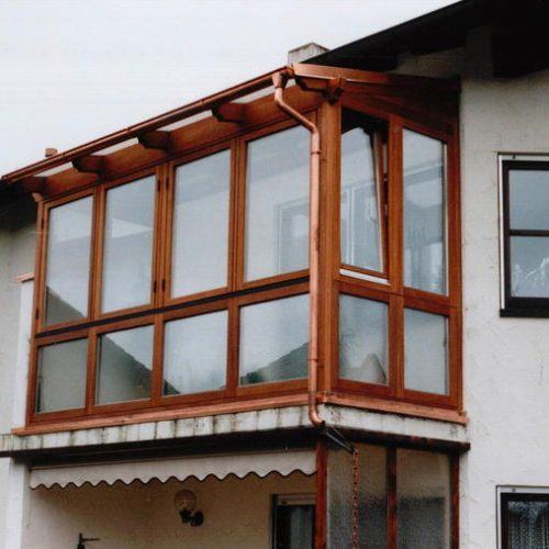 Holzbalkon mit großen Fenstern