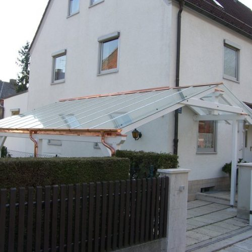 weißes Carport mit Glasdach und Kupferelementen
