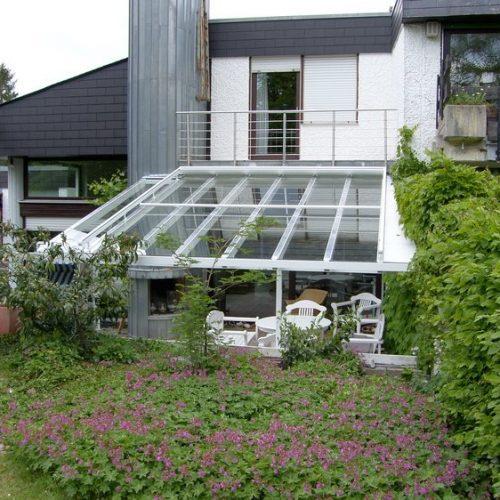 schräge Terrassenüberdachung mit großen Glaselementen