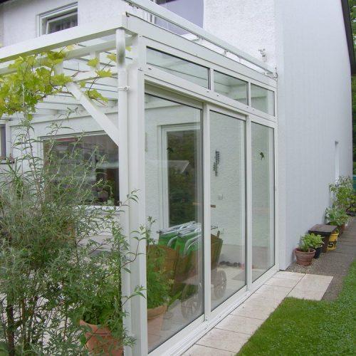 Weiße Terrassenüberdachung mit seitlichen Glaswänden