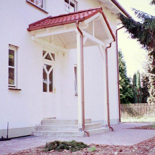 Haustür mit weißem, spitzem Vordach und roten Dachziegeln
