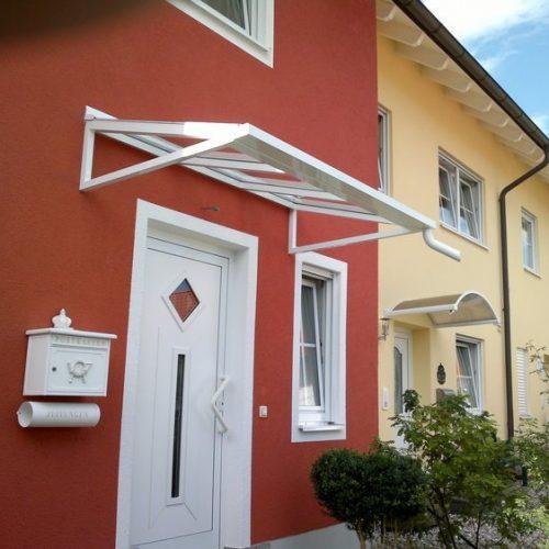weißes Haustürvordach an rotem Haus