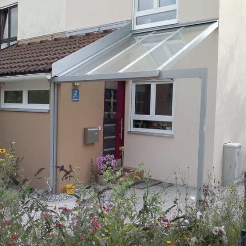 Haustüre mit Glasvordach und hellem Aluminium