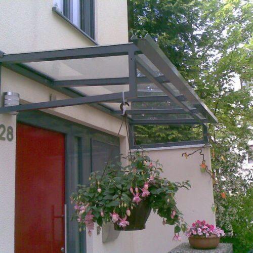 Vordach aus grauem Aluminium vor roter Haustüre