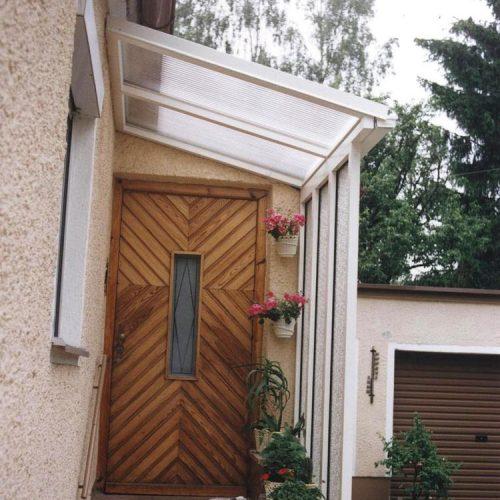 weißes Vordach vor brauner Holztüre
