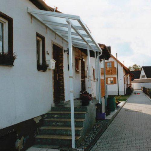 weißes Vordach schützt Treppenaufgang