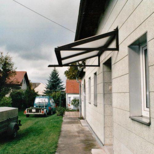 Haustürvordach aus Glas und schwarzem Aluminium