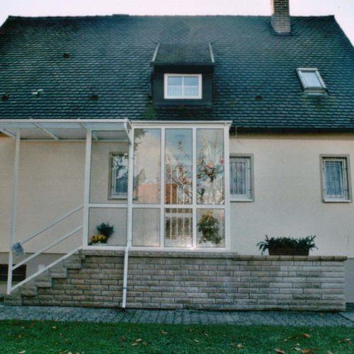 Vordach mit Seitenelementen aus Glas schützt Treppenaufgang und Haustüre