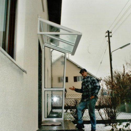 Zufriedener Mann präsentiert neues Vordach vor Eingangsbereich