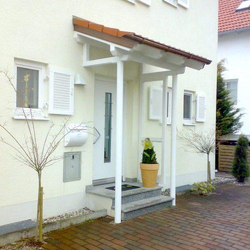 weißes Haustürvordach aus Holz mit roten Dachziegeln