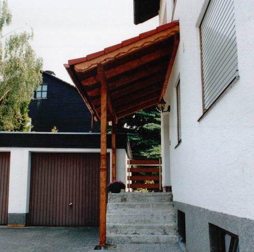 Haustüre und Treppenstufen mit Vordach aus Holz
