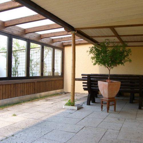 Wintergarten von innen mit Holzgestell und Beschattung