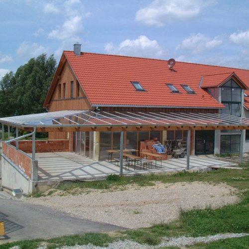 Bau eines großen Wintergartens aus Holz mit Glasüberdachung