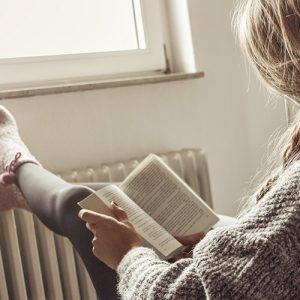 Junge Frau schaut aus dem Fenster, trinkt Tee und legt Füße zu