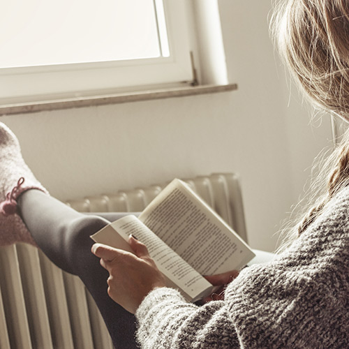 Füße auf Heizung und Buch als Symbol für Gemütlichkeit