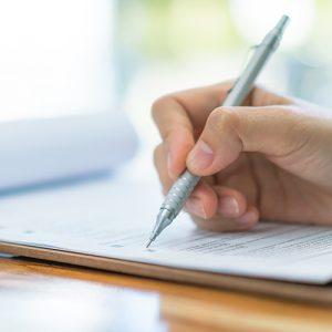Papier und Stift in Hand als Symbol für Antrag