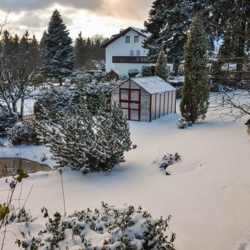 Wintergarten im schneebedeckten Garten