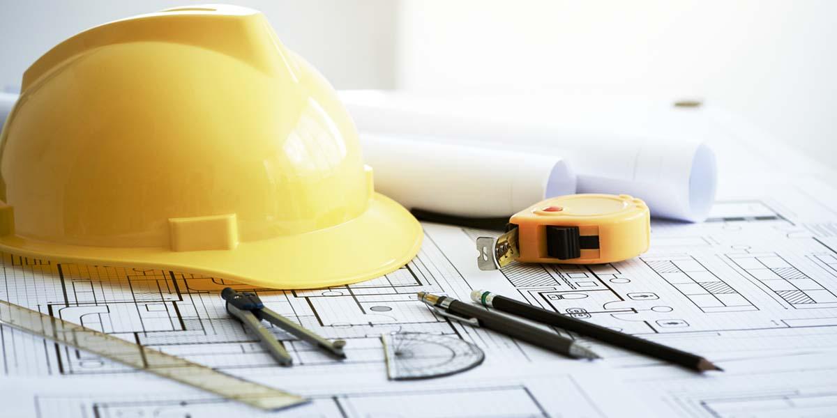 Gelber Bauarbeiterhelm auf Bauzeichnung mit Baugenehmigung